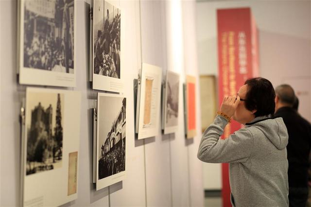 A visitor looks at photos at the exhibition at Qian Xuesen Library and Museum on Tuesday.